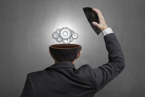 Working metal gears inside businessman head in gray concrete wall background
